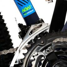 Packshot produit d'un vélo tout terrain photographié en studio sur fond blanc pour du packshot publicitaire. Gros plan sur le dérailleur avant.