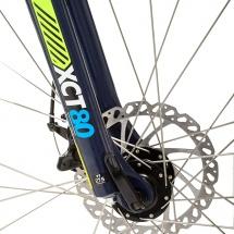 Packshot produit d'un vélo tout terrain photographié en studio sur fond blanc pour du packshot publicitaire. Détail de la fourche et du moyeu avant.